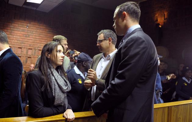 Oscar Pistorius (D) parle avec sa soeur Aimee, le 4 juin 2013 avant de comparaître devant un tribunal de Pretoria [Alexander Joe / AFP]