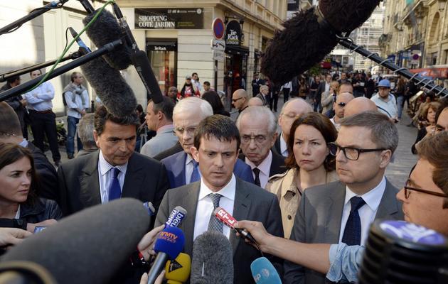 Le ministre de l'Intérieur Manuel Valls (c), le 6 juin 2013 à Paris, sur les lieux de la bagarre mortelle [Bertrand Guay / AFP]