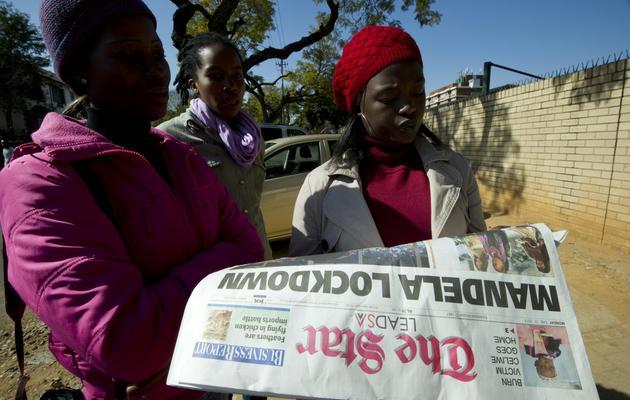 Mandela à la Une d'un quotidien sud-africain que lisent des jeunes femmes le 10 juin 2013 devant l'hôpital spécialisé de Pretoria [Alexander Joe / AFP]