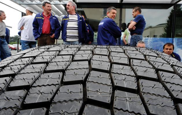 Des salariés de Michelin derrière un pneu, le 10 juin 2013 à Joué-lès-Tours (en Indre-et-Loire) [Jean-Francois Monier / AFP]