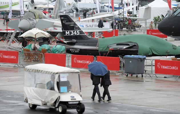 Des visiteurs arrivent au salon du Bourget le 17 juin 2013 sous la pluie [Eric Piermont / AFP]