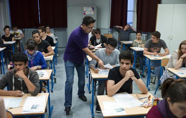Un surveillant distribue les épreuves de philosophie, le 17 juin 2013 au Lycée Arago à Paris [Fred Dufour / AFP]