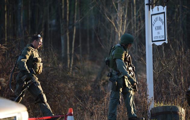 Les forces de sécurité vérifient les abords de l'école primaire de Newtown, dans le Connecticut où une fusillade a fait 27 morts, le 14 décembre 2012 [Don Emmert / AFP]