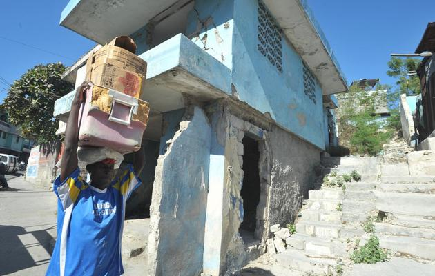 Un homme passe le 11 janvier 2013 à côté d'une maison de Port-au-Prince détruite par le séisme de janvier 2010 [Thony Belizaire / AFP]