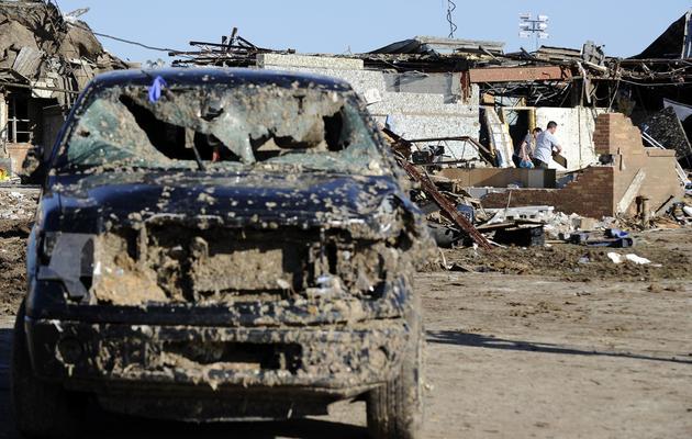 Des habitants de Moore le 22 mai 2013 au milieu des décombres de leurs maisons détruites [Jewel Samad / AFP]