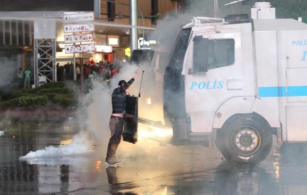 Un manifestant face à un car de police dispersant des gaz lacrymogènes  le 8 juin 2013 à Ankara [Adem Altan / AFP]