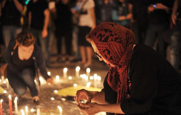 Une femme turque allume une bougie lors d'un rassemblement en hommage aux personnes mortes lors des manifestations place Taksim, à Istanbul, le 14 juin 2013 [Ozan Kose / AFP]