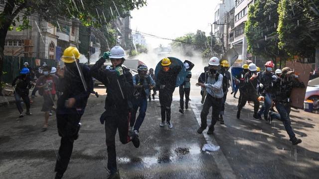 Des manifestants à Rangoun fuient les gaz lacrymogènes lancés par la police.