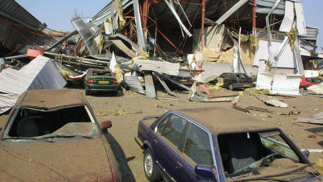 Des voitures sont coincées, le 21 septembre 2001, sous les décombres d'un centre commercial près de l'usine chimique AZF, près de Toulouse [Dominique Faget / AFP/Archives]