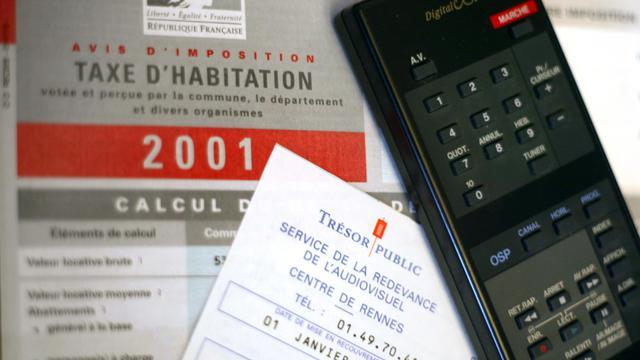 Une télécommande, une fiche de redevance télé et une de la taxe d'habitation datant de 2001. [Martin Bureau / AFP/Archives]