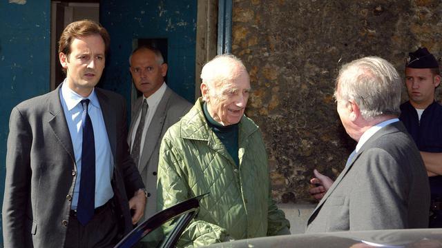 Maurice Papon (c) sort de prison le 18 septembre 2002 à Paris, accueilli par ses avocats, Mes Francis Vuillemin (G) et Jean-Marc Varaut (d) [Jack Guez / AFP/Archives]