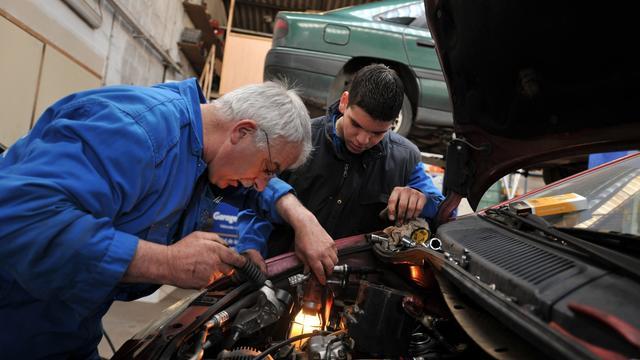 Deux mécaniciens réparent une voiture [Mychele Daniau / AFP/Archives]