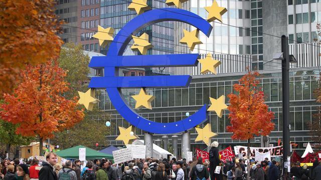 Une foule sous le logo de l'euro devant la Banque centrale européenne (BCE), à Francfort, en 2011 [Daniel Roland / AFP/Archives]