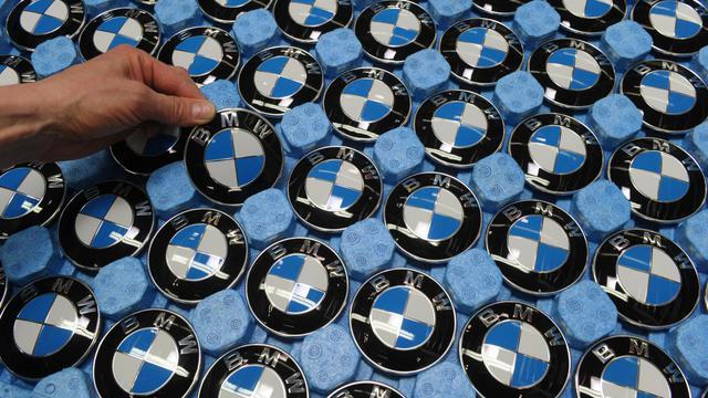 Un employé saisit un logo BMW pour l'apposer sur une voiture [Christof Stache / AFP/Archives]
