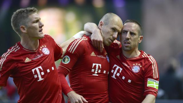 L'attaquant français Franck Ribéry (D) enlasse son coéquipier néerlandais Arjen Robben (M), à côté du milieu allemand Bastian Schweinsteiger (G), lors du match du Bayern Munich contre le Borussia Dortmund, le 12 mai 2012 [Odd Andersen / AFP/Archives]