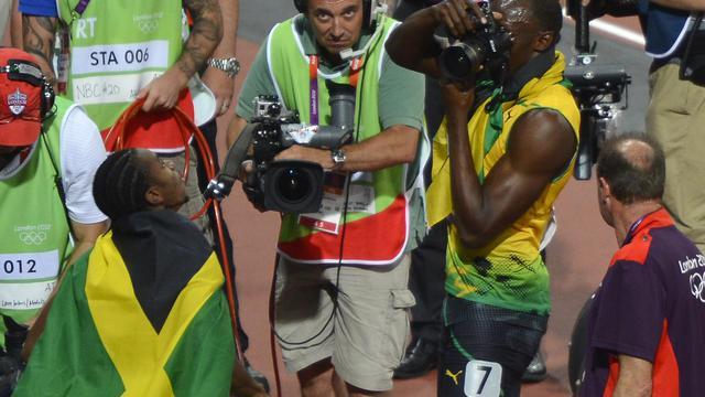 Usain Bolt prend des photo après son sacre olympique aux Jeux de Londres, le 9 août 2012. [Odd Andersen / AFP/Archives]