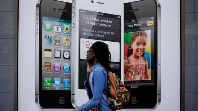 Une femme parlant au téléphone passe devant une publicité pour des mobiles [Andrew Cowie / AFP/Archives]