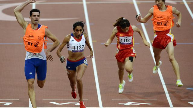 Quand Gautier Simounet a franchi la ligne d'arrivée avec Assia El Hannouni, médaille d'or au 200 m, il a levé les bras en signe de triomphe car cette victoire, c'est aussi un peu la sienne, lui qui a couru la main attachée à celle de l'athlète malvoyante pour guider sa foulée [AFP]