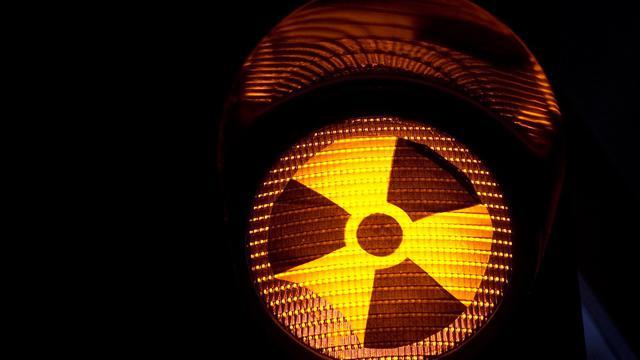Le symbole de la radioactivité apparaît en transparence sur un feu de signalisation [Johannes Eisele / AFP/Archives]