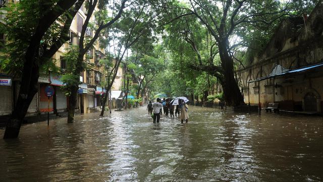 Des piétons marchent dans l'eau à Bombay le 27 août 2012 [Punit Paranjpe / AFP/Archives]