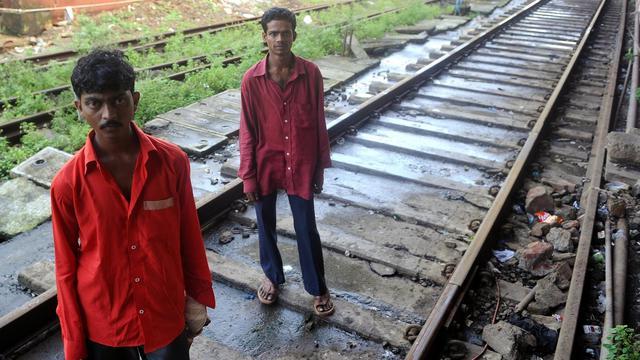 Pour quelques malheureuses roupies, tout juste le prix du détergent qu'ils sniffent afin de chasser les fantômes, Ravi et Harish ramassent les cadavres déchiquetés par les trains sur les voies mortifères de Bombay. [AFP]