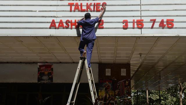 """Une personne installe l'annonce de la projection du film """"Bombay Talkies"""", le 3 mai 2013 devant un cinéma de Bombay [Indranil Mukherjee / AFP/Archives]"""