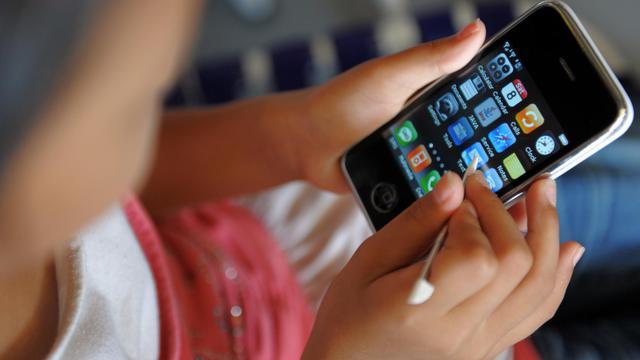 Un smartphone utilisé par un enfant [Tang Chhin Sothy / AFP/Archives]