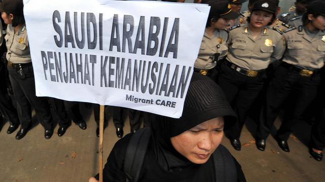 """Un militant indonésien porte une pancarte où est inscrit """"L'Arabie saoudite criminelle contre l'humanité"""" pour protester contre une exécution, à Jakarta, le 21 juin 2011 [Adek Berry / AFP/Archives]"""