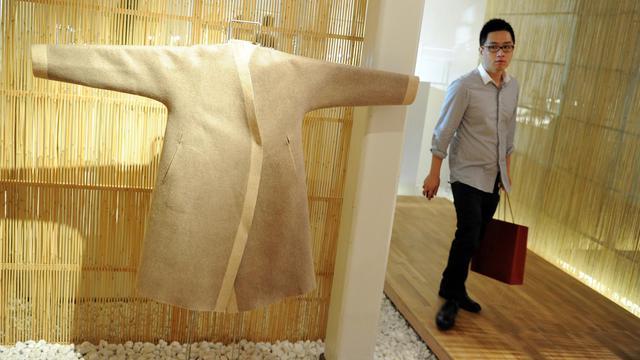 Un homme passe près d'un vêtement de la marque Shang Xia le 15 septembre 2011 à Shaghaï [Mark Ralston / AFP/Archives]