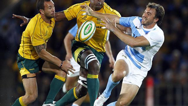 Les Australiens Quade Cooper (g) and Radike Samo (c) aux prises avec l'Argentin Juan Martin Hernandez (d) lors d'un match du Four Nations à Queensland (Australie), le 15 septembre 2012. [Patrick Hamilton / AFP/Archives]