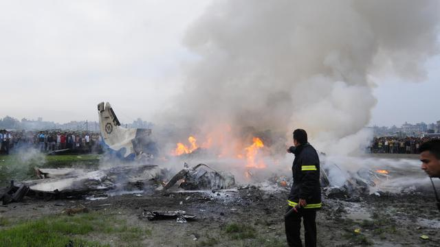 Des pompiers éteignent le feu qui embrase la carcasse de l'avion qui s'est écrasé le 28 septembre 2012 près de Katmandou [ / AFP]