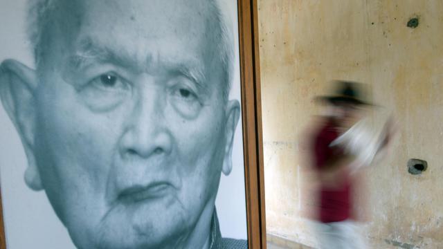 Un touriste passe devant un portrait de Nuon Chea, l'idéologue des Khmers rouges, au musée Tuol Sleng de Phnom Penh, le 29 mars 2013 [Tang Chhin Sothy / AFP/Archives]