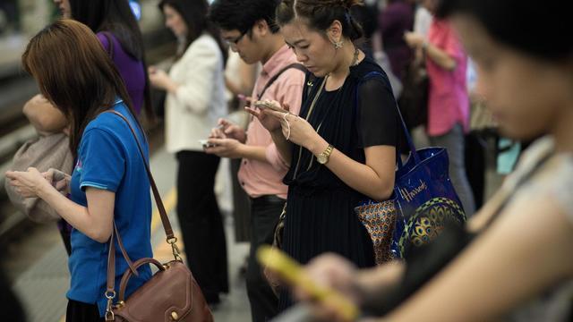 Des Thaïlandais regardent leurs téléphones portables [Nicolas Asfouri / AFP/Archives]