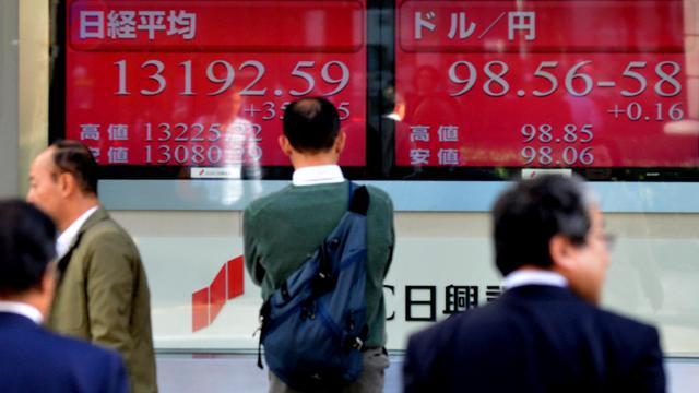 Des passants dans une rue de Tokyo devant un panneau affichant le taux de change entre le yen et le dollar, le 8 avril 2013 [Kazuhiro Nogi / AFP/Archives]