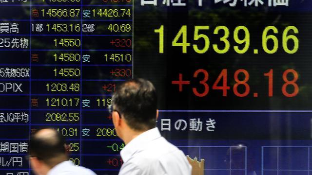 Des Japonais passent devant un tableau avec les indices de la Bourse de Tokyo [Toru Yamanaka / AFP/Archives]