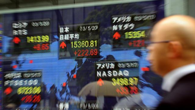 Un homme passe devant un panneau indiquant les cours de la bourse, à Tokyo, le 20 mai 2013 [Yoshikazu Tsuno / AFP]