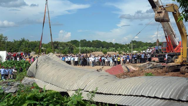 Des personnes regardent le toit d'une usine textile sur le sol après l'effondrement d'une dépendance, le 20 mai 2013 à Phnom Penh [Tang Chhin Sothy / AFP]