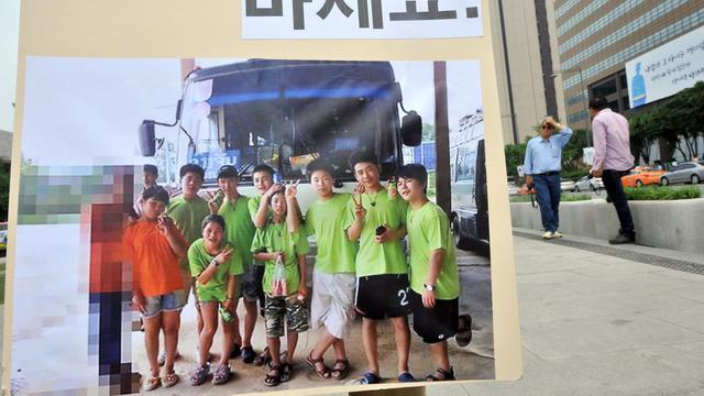 Un militant montre le 3 juin 2013 à Séoul,une photo des 9 jeunes Nord-Coréens enfuis au Laos et reconduits chez eux de force [Jung Yeon-Je / AFP]