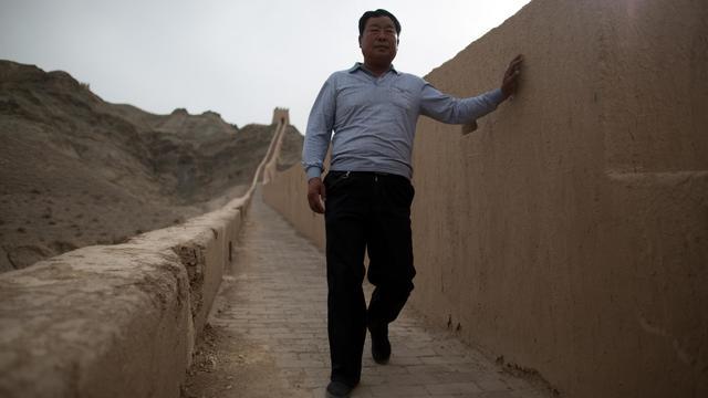 Yang Yongfu pose devant un morceau de la Grande Muraille de Chine qu'il a lui-même restauré, le 14 mai 2013 [Ed Jones / AFP]