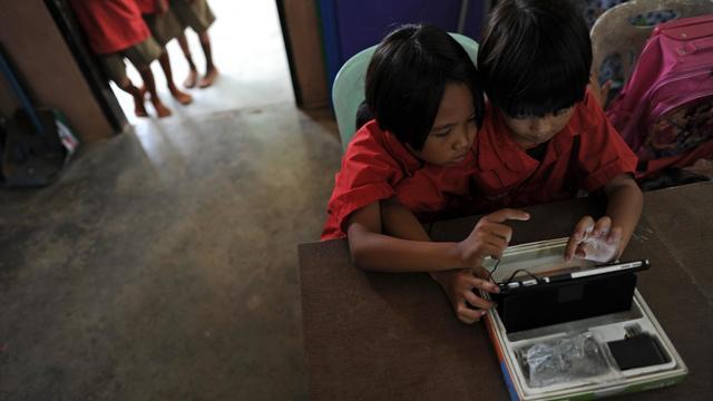 Des écolières utilisent une tablette à l'école Ban San Kong de Mae Chan, en Thaïlande, le 27 mai 2013 [Christophe Archambault / AFP]