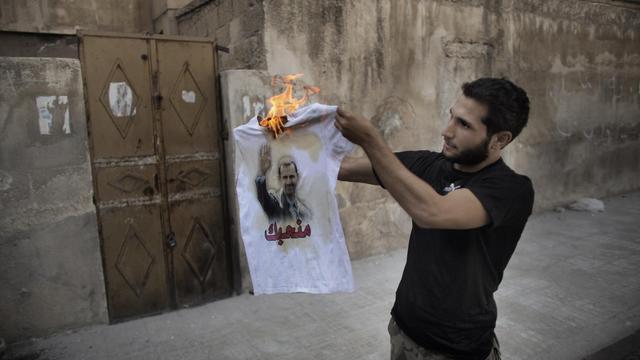 Un rebelle syrien brûle le portrait du président Bachar al-Assad, le 12 septemnre 2012 à Alep. [Marco Longari / AFP/Archives]