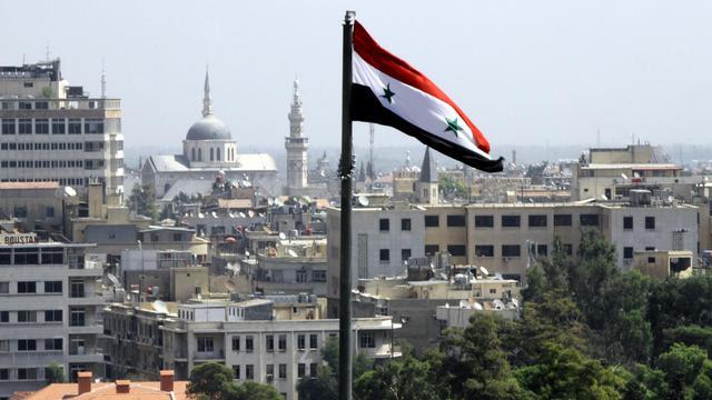 Le drapeau syrien flotte sur Damas [Louai Beshara / AFP/Archives]
