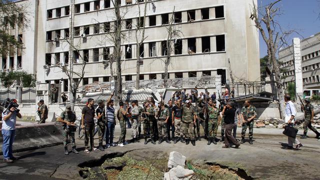 Des soldats syriens se tiennent autour du cratère laissé par une bombe près du bâtiment de l'état-major à Damas, le 26 septembre 2012 [Louai Beshara / AFP]