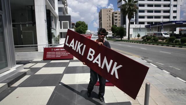 Un travailleur emporte l'enseigne de la banque Laiki après la faillite d'une agence, le 16 mai 2013 à Nicosie [Yiannis Kourtoglou / AFP/Archives]