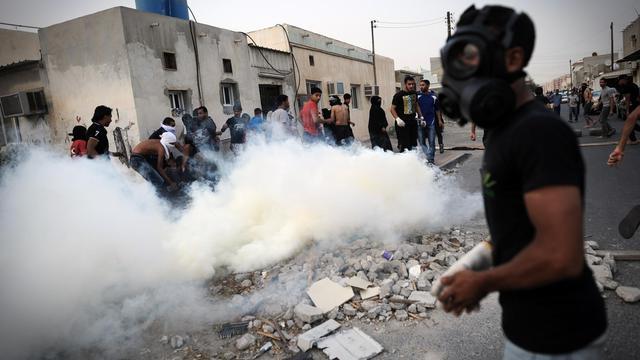 Des manifestants se protègent de gaz lacrymogènes tirés par la police anti-émeutes, le 1er juin 2013  dans un village au sud de Manama, au Bahreïn [Mohammed al-Shaikh / AFP/Archives]
