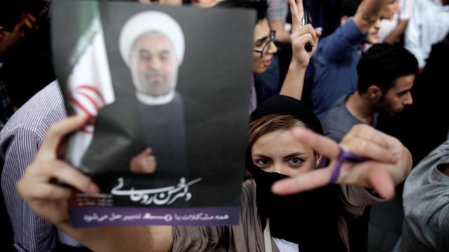Une femme iranienne fait le V de la victoire en brandissant une photo de Hassan Rohani, le 15 juin 2013 à Téhéran [Behrouz Mehri / AFP]