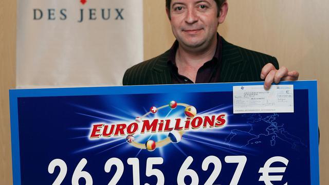 Pascal Brun pose, le 21 décembre 2004 à Boulogne-Billancourt, avec le chèque de 26.215.627 euros gagné à l'Euro Millions [Jack Guez / AFP/Archives]