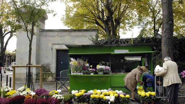 Des personnes achètent des fleurs avant la Toussaint devant un cimetière de Paris [Stephane de Sakutin / AFP/Archives]