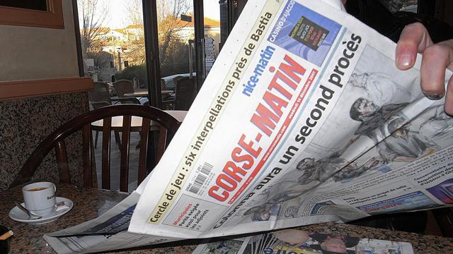Un homme lit Corse-Matin, à Cargèse en 2007 [Stephan Agostini / AFP/Archives]