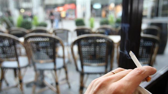 Un client fume une cigarette à une terrasse d'un café chauffée par des braseros, le 30 décembre 2007 dans le quartier des Halles à Paris. [Patrick Hertzog / AFP/Archives]